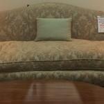 Upholstered olive green floral print sofa