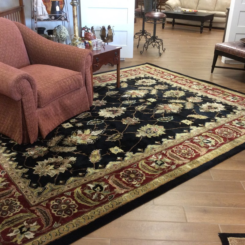 This handsome rug is quite large, measuring 9ft. by 12 ft. The colors include black, brick, gold, tan and cream, as well as some pink, blue and green. Stop by and see it for yourself!