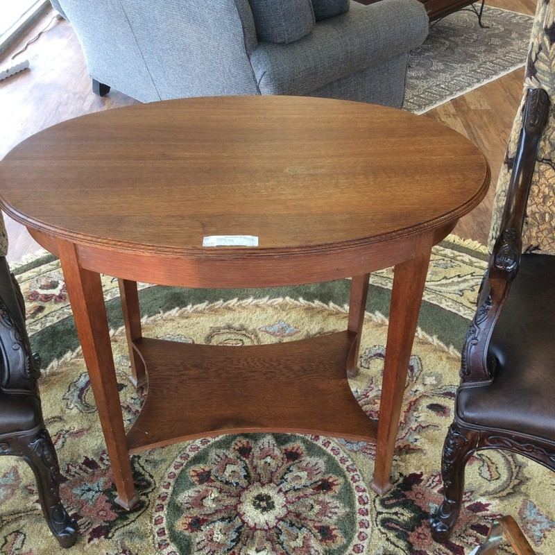 This is a very simple, older, oval-shaped oak table. Although it shows signs of wear it is still very good condition. It features solid oak construction and even has a lower display shelf!