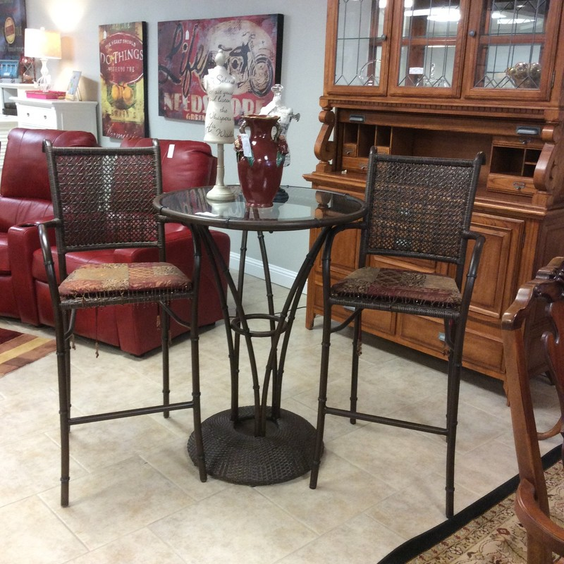 This is a very nice bistro table with 2 chairs. The table is a combination of metal and wicker with  a glass top. The chairs have a thin upholstered seat cushion with a beaded fringe and can be used with or without the seat cushions. Come take a look!