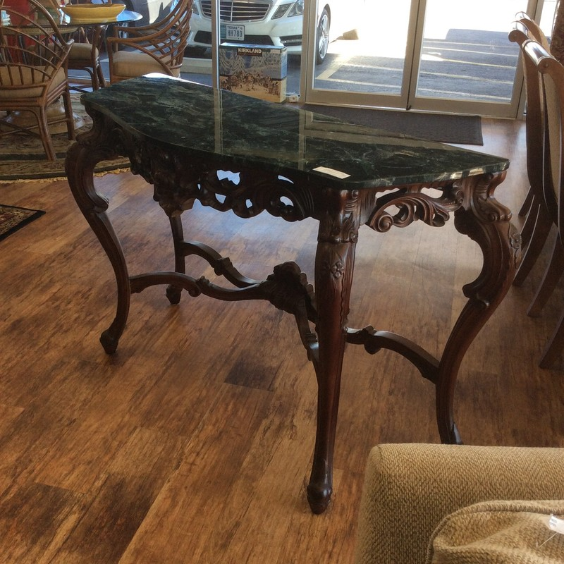 This ornate entryway table is constructed of a rich, dark wood with a green and black marble tabletop. The base of the table is heavily carved giving it a more traditional  and dramatic look.