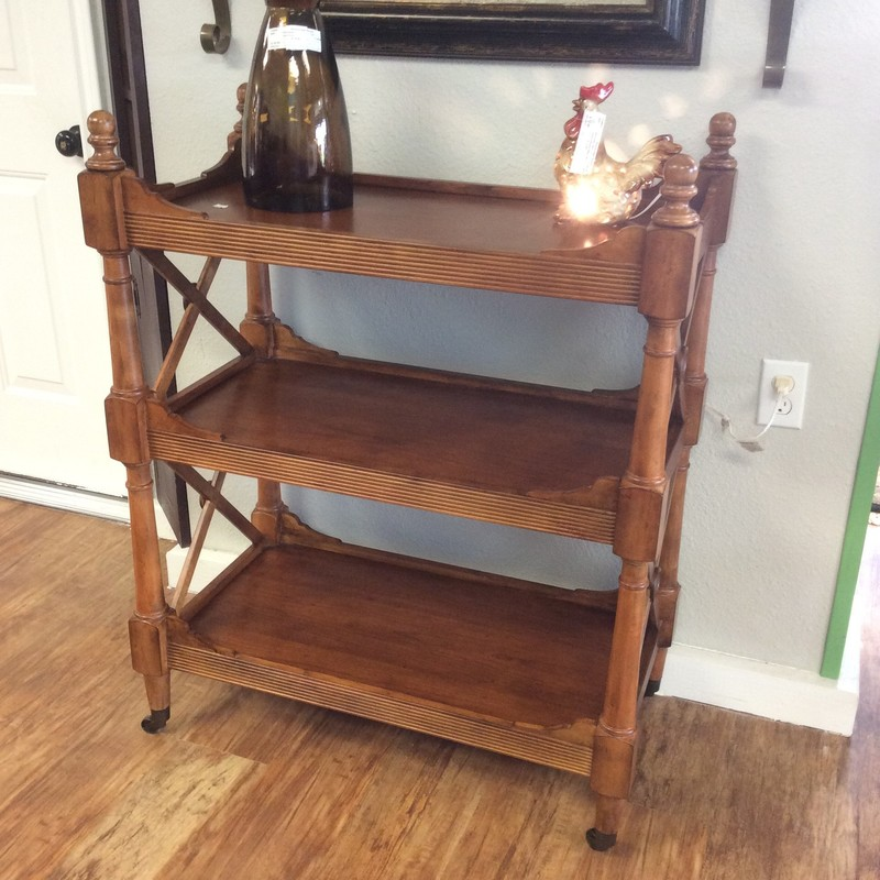 This is a smart and handsome serving cart! It features solid wood construction, 3 spacious shelves, and pretty carved details. Also, it's on casters, making it portable!